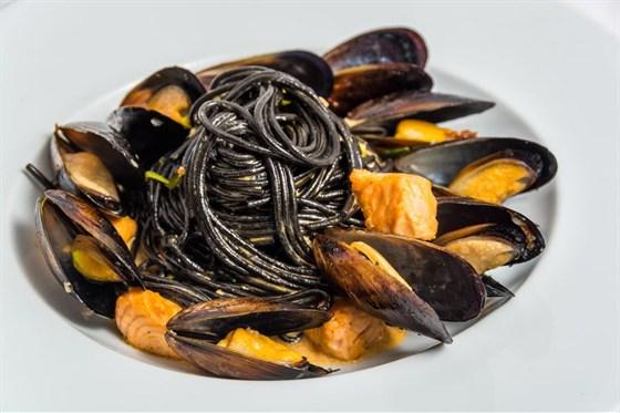 Ресторан Де Марко - фотография 3 - Черные спагетти с мидиями- черные спагетти с мидиями, тушеные в белом вине, с луком порей, норвежским лососем в сливочно-томатном соусе.