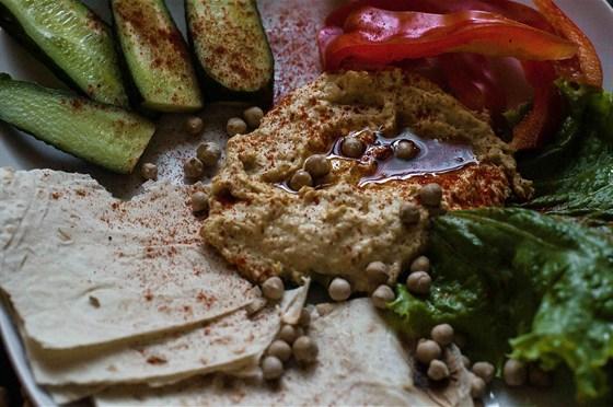 Ресторан Среда - фотография 4 - Хумус. Краеугольный камень ближневосточной кухни, он же закуска, он же основное блюдо, он же салат, он же бедуинский соус. Пюре из нута с зирой, растертым кунжутом, лимонным соком, нерафинированным оливковым маслом, паприкой и петрушкой. Подается с огурцом, томатами и лавашем.